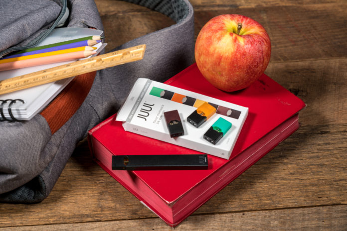 bookbag on wood desk with vape and a apple beside it on top of a book
