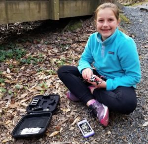 Georgia girls' STEM program; young girl sitting on ground with phone and tech kit