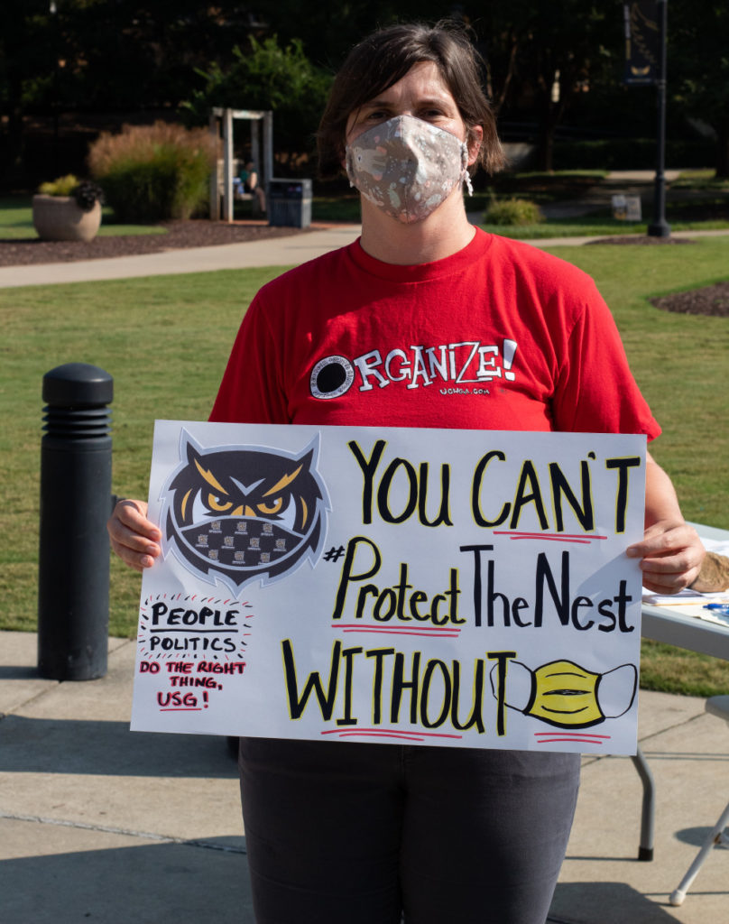 mask mandate protest for COVID-19 on college campus; woman in red shirt holds sign declaring 'you can't protect the nest without a mask'