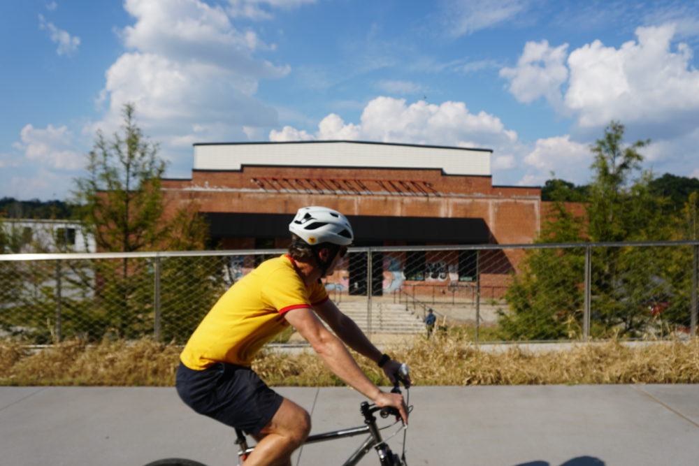 A bicyclist wearing a yellow shirt passing a build with Pittsburg Yards on the side